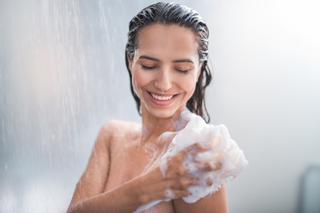 笑顔で体を洗う女性