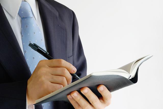 手帳を書く男性