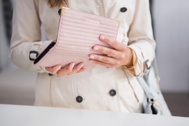ピンクの財布を使う女性