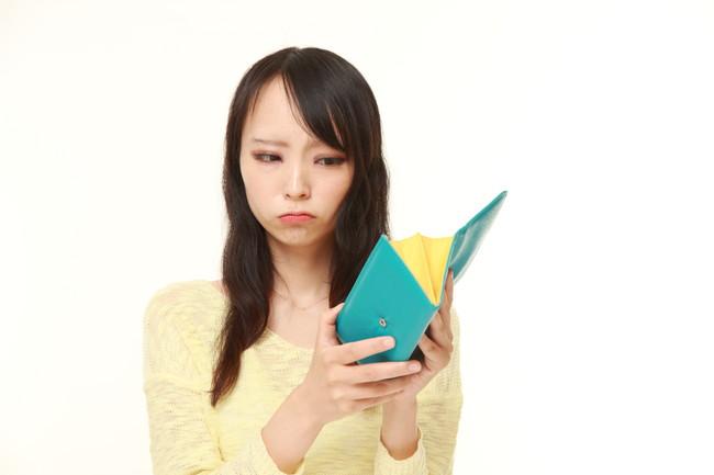 空の財布を持つ女性