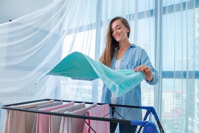 室内で洗濯物を干している女性