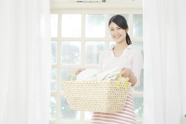 洗濯カゴを持っている笑顔の女性