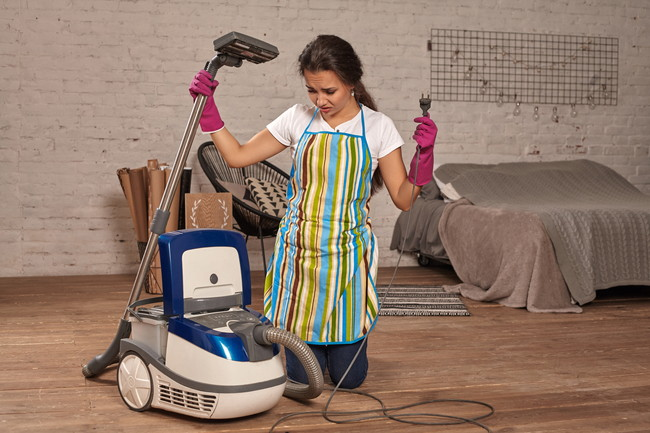 掃除機を持って困っている様子の女性