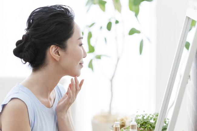 鏡を見ながらスキンケアをするミドル女性