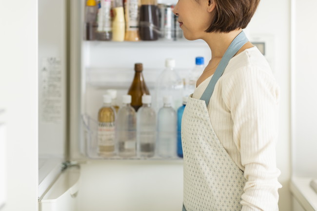 冷蔵庫の前に立つ主婦