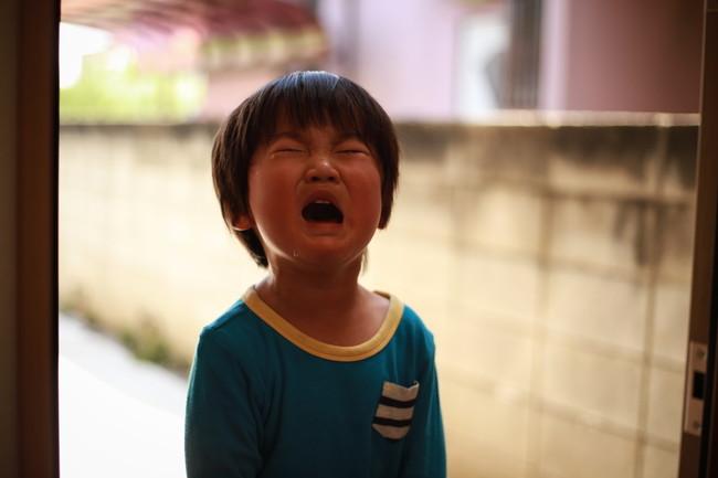 玄関先で泣く子ども