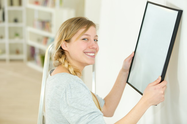 絵画を飾ろうとする女性