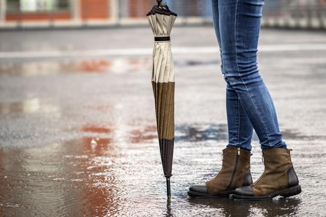 閉じた傘を持つ女性