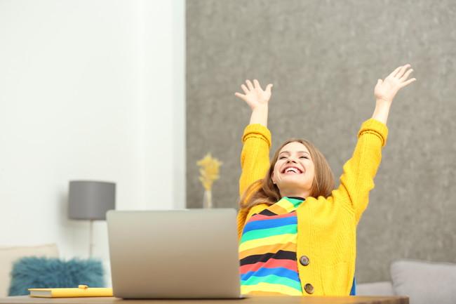 パソコンの前で喜んでいる女性