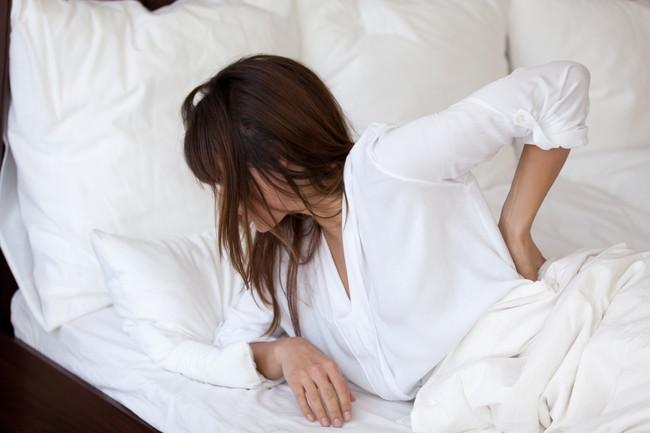 腰を抑えながら起きる女性