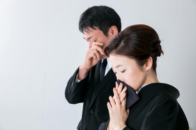 お葬式で泣男性と女性