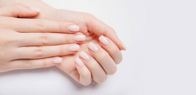 ナチュラルカラーのネイルをしている女性の爪