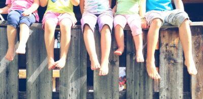 裸足で並んで座っている子供たち