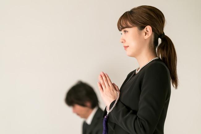 葬儀で手を合わせる女性