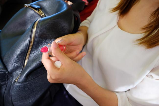 電車内で化粧をする女性