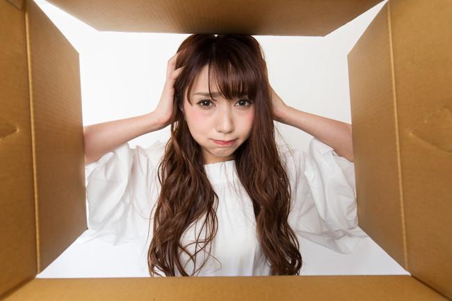 箱を覗いて頭を抱える女性