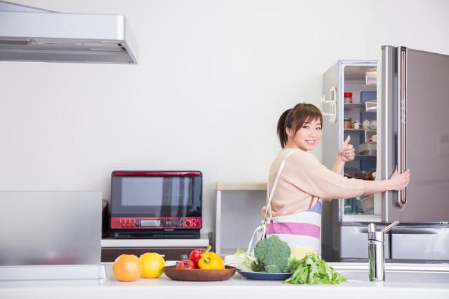 冷蔵庫を開いて嬉しそうな女性