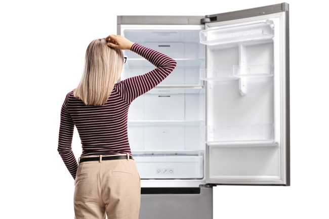 冷蔵庫を見て頭を抱える女性