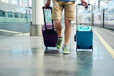 スーツケースを引いて歩く男性