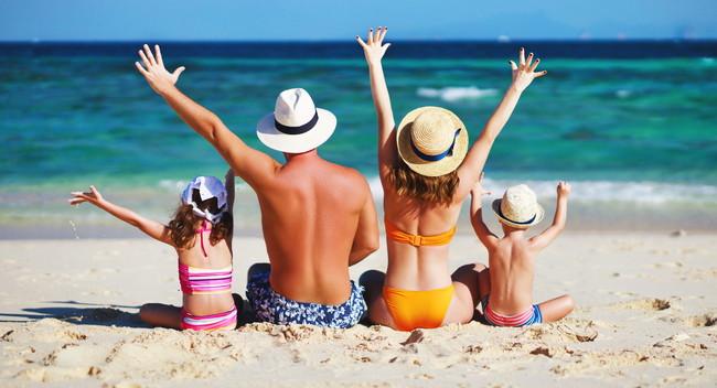 ビーチで日焼けをしている家族の後ろ姿