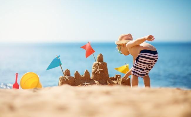 海辺で砂遊びをする小さな男の子