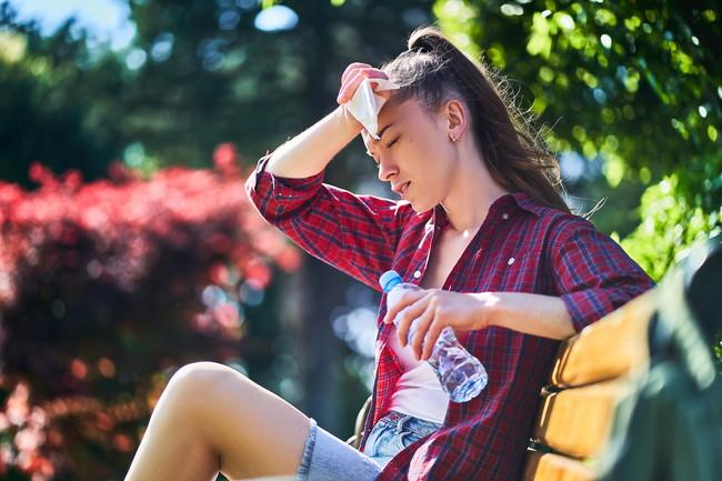 暑さの中ベンチで休んでいる女性