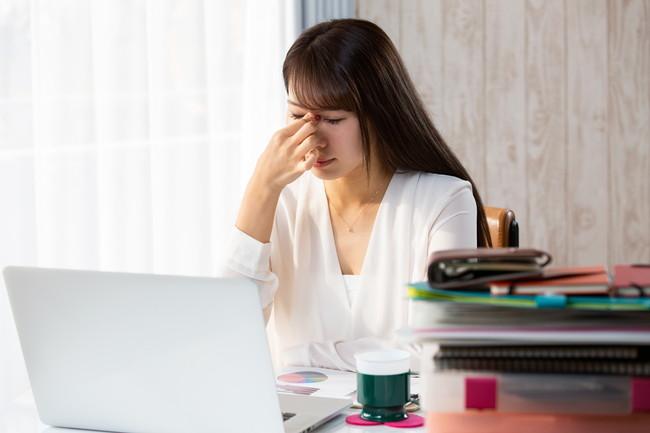 パソコンで疲れ目の女性