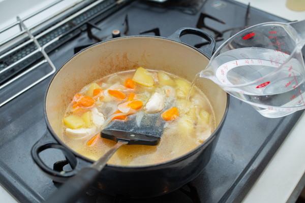 炒めた野菜に水を加える様子