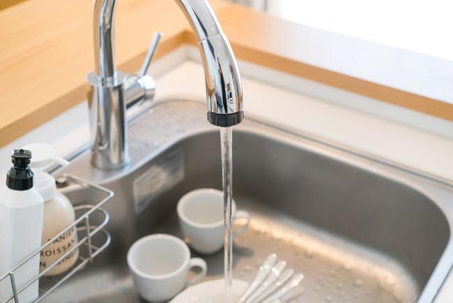 食器を洗うために水を出す様子