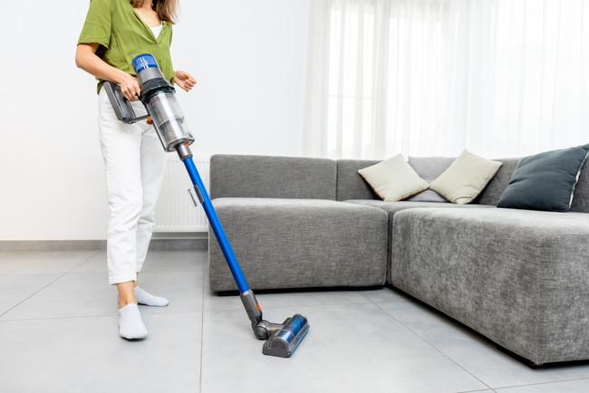 青い掃除機を使う女性