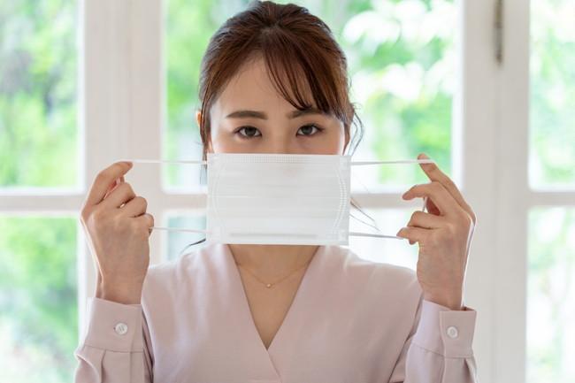 マスクで口を覆う女性