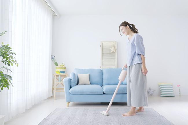 掃除機をかけて部屋をきれいにする女性