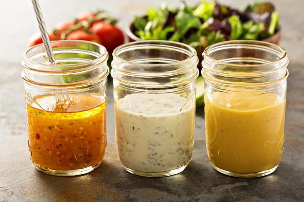 3種類のドレッシング、背後に野菜のサラダ
