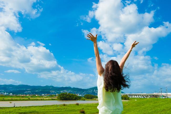 青空に向かって手を広げる一人の女性