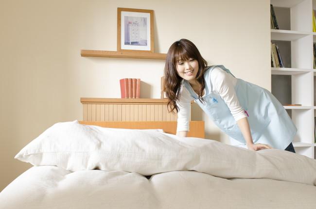 ベッドメイキングをする女性