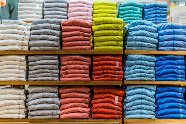 カラフルな服が並べ得られた商品棚