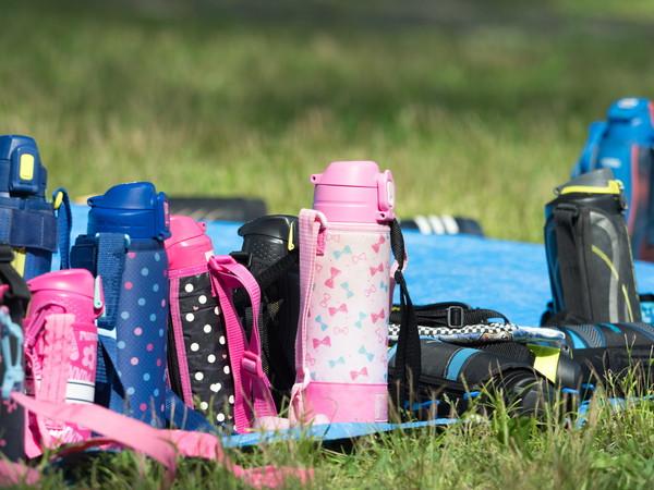 芝生に置かれた子供たちの水筒