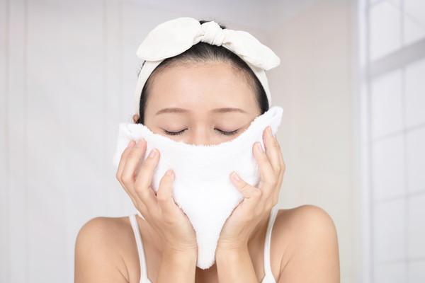顔にタオルを当てる女性