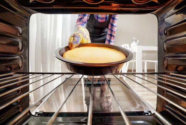 キッチンのオーブンからチーズケーキを取り出す主婦