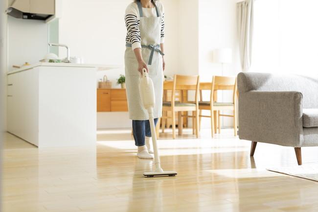 リビングルームを掃除機をで掃除をしている女性