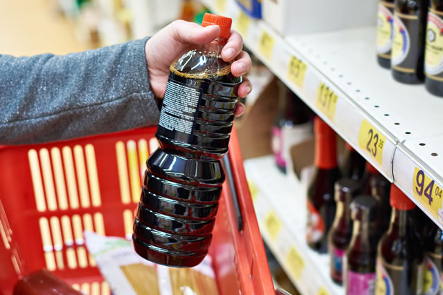 Soy sauce bottle in hand buyer at grocery store