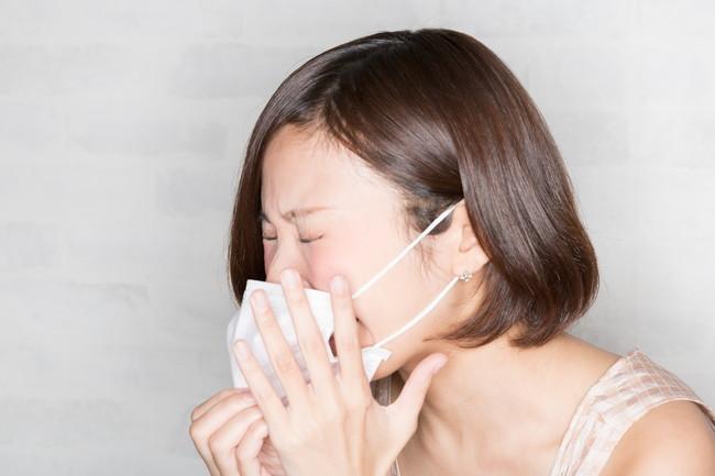 マスクをしながらくしゃみをしている女性