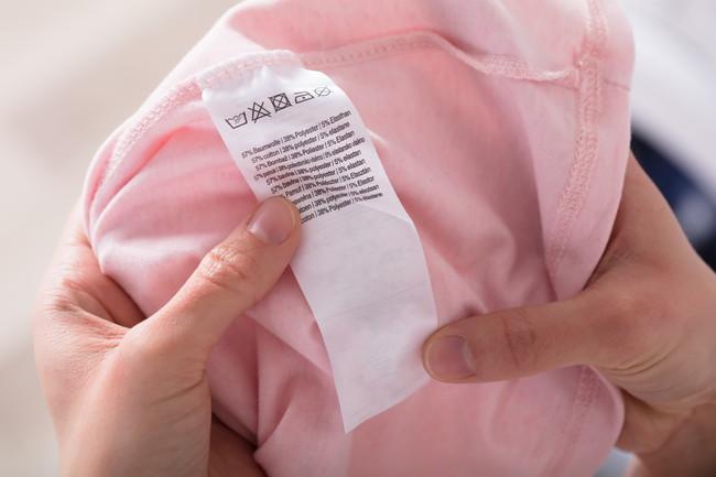 洋服に付いている洗濯表示を確認している
