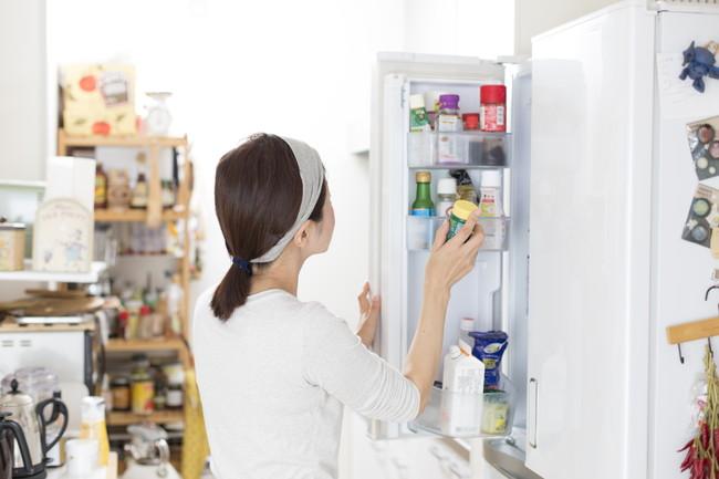 冷蔵庫を開けて調味料を取り出している女性