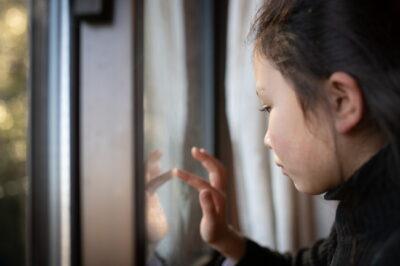 窓に指で落書きをする少女