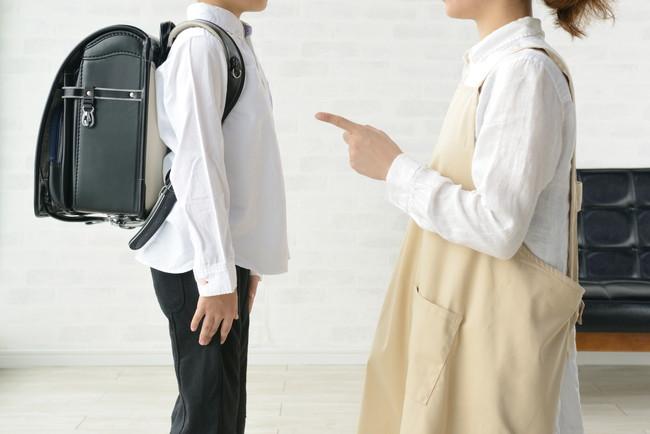 小学生の子どもを叱る母親