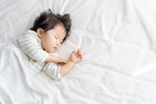 布団の上で昼寝をしている子供