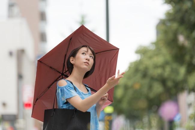 傘を肩にかけてさしている女性
