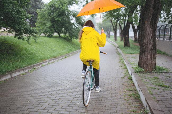 傘をさしながら自転車に乗っている女性