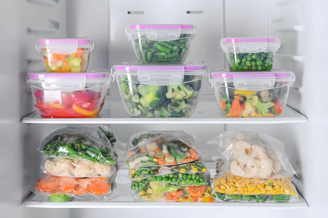 ontainers and plastic bags with frozen vegetables in refrigerator